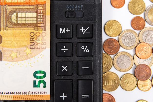 Primer plano de monedas de euro, billetes y calculadora, concepto de planificación financiera