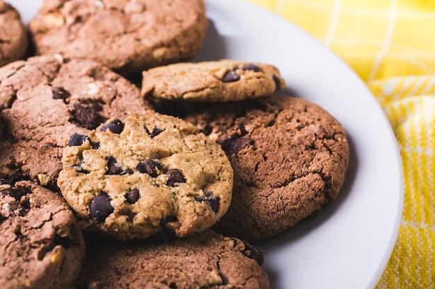 Primer plano de un montón de galletas con chispas de chocolate en una placa blanca.