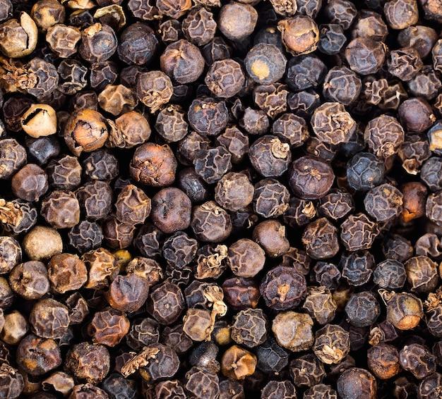 Primer plano de un montón de granos de pimienta negra seca