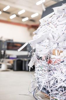Primer plano del montón de papeles cortados producidos con máquina de linotipo en la imprenta