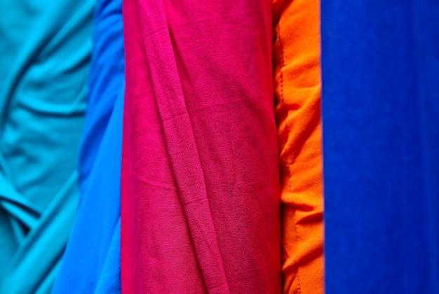 Primer plano de los montones de telas y telas de colores en una tienda