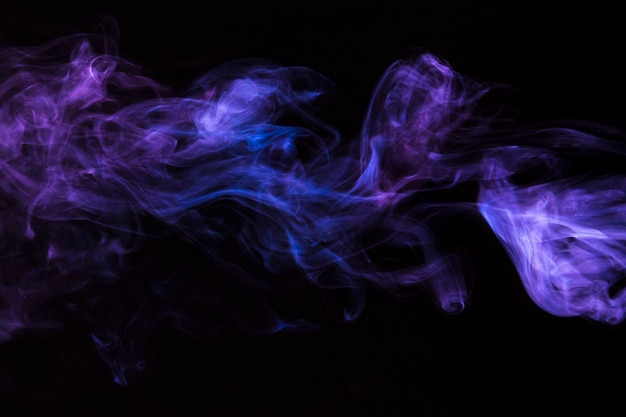 Primer plano del movimiento del humo púrpura sobre fondo negro