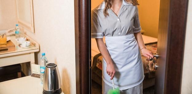 Primer plano de mucama sosteniendo el plumero en la mano de pie en la entrada de la habitación del hotel