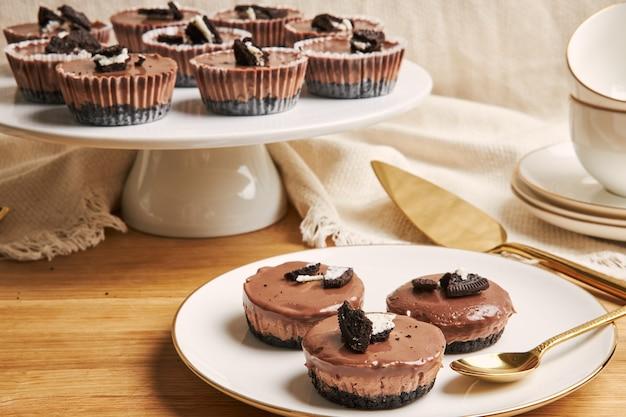 Primer plano de muffins de chocolate cremoso con coberturas de galletas en platos bajo las luces