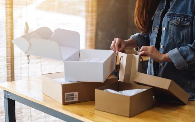 Primer plano de una mujer abriendo y mirando dentro de la bolsa de compras en casa para la entrega y el concepto de compra en línea