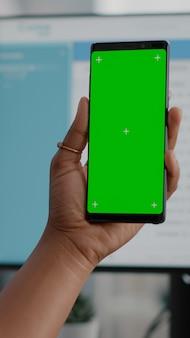 Primer plano de mujer africana sosteniendo simulacros de pantalla verde chroma key teléfono con pantalla aislada en manos con reunión de conferencia de video llamada en línea. estudiante trabajando de forma remota desde casa viendo videos