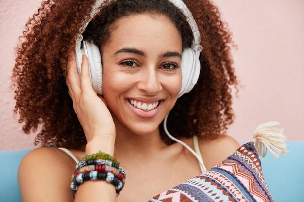 Primer plano de una mujer afroamericana de piel oscura de aspecto agradable escucha audiolibro en auriculares