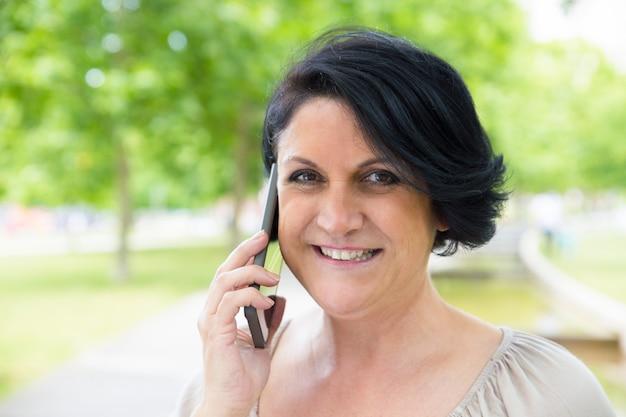 Primer plano de mujer alegre hablando en celular al aire libre