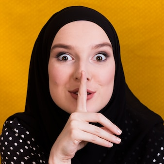 Primer plano de una mujer árabe haciendo gesto silencioso sobre fondo