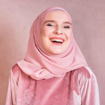 Primer plano de una mujer árabe joven alegre con velo