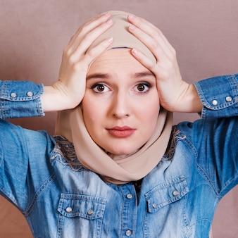 Primer plano de una mujer árabe triste que tiene dolor de cabeza