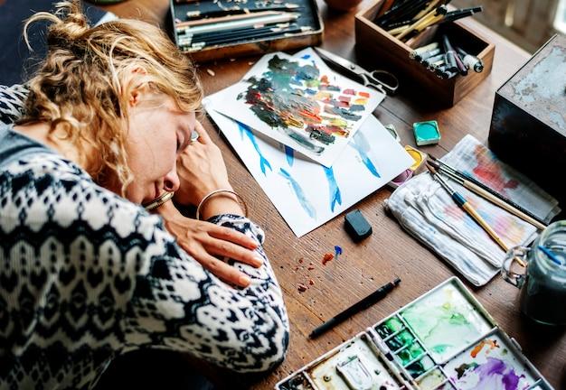 Primer plano de la mujer artista tomando una siesta en la mesa de trabajo