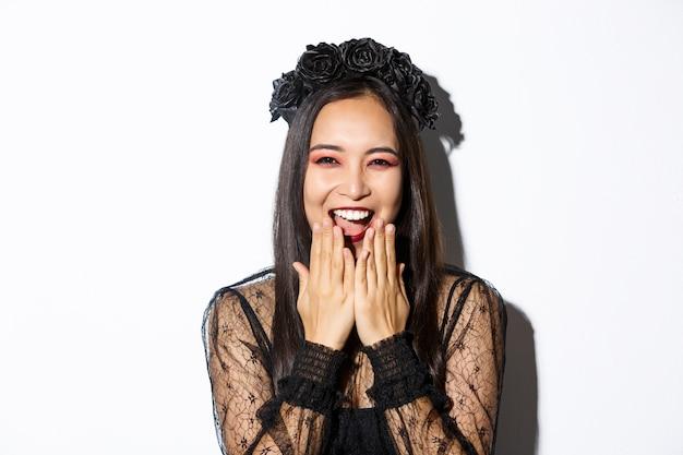 Primer plano de mujer asiática feliz celebrando halloween en traje de bruja y riendo, de pie sobre fondo blanco.