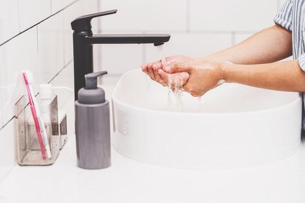 Primer plano de mujer asiática lavarse las manos con agua del grifo en el baño en casa