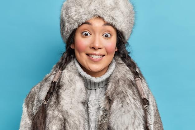Primer plano de una mujer asiática sorprendida con dos coletas vestidas con prendas de vestir exteriores de piel gris sonríe gratamente vive en un lugar ártico aislado sobre una pared azul