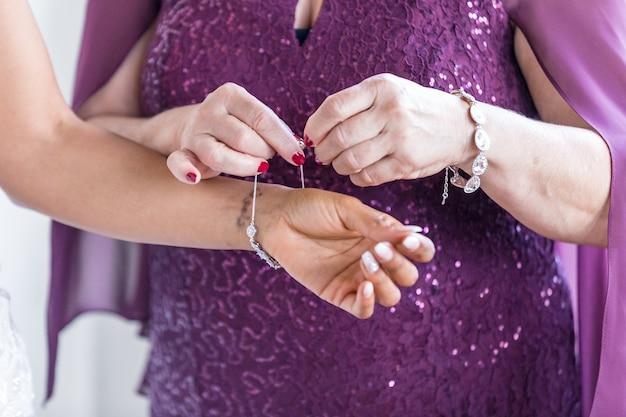 Primer plano de una mujer asistida por otra mujer para ponerse sus joyas