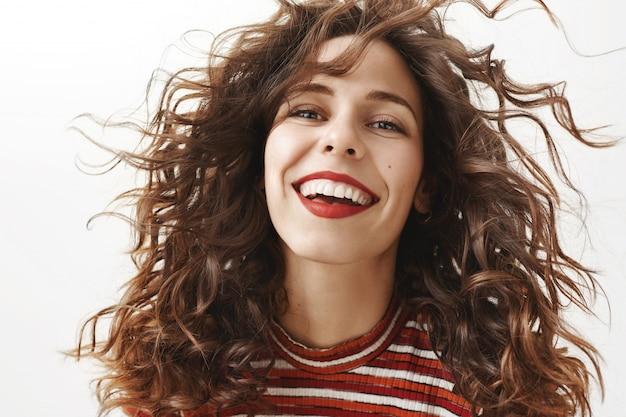 Primer plano de mujer atractiva despreocupada con pelo rizado sonriendo