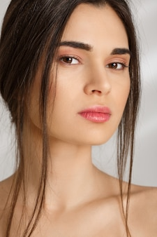 Primer plano de mujer atractiva con maquillaje natural en la pared gris
