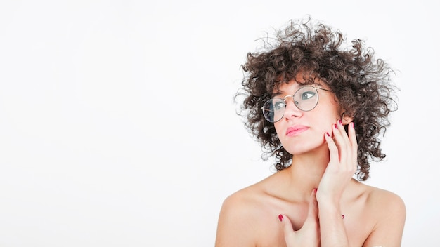 Primer plano de una mujer atractiva tocando su mejilla suavemente