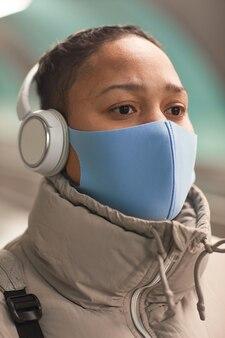 Primer plano de mujer en auriculares inalámbricos y máscara protectora escuchando música