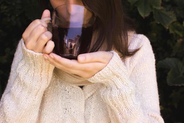 Primer plano de una mujer bebiendo la taza de té de hierbas
