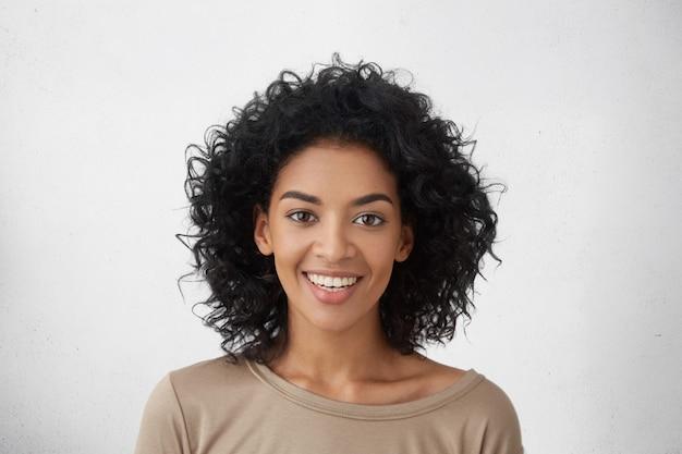 Primer plano de una mujer bonita con dientes perfectos y piel oscura y limpia descansando en el interior, sonriendo felizmente después de recibir buenas noticias positivas.