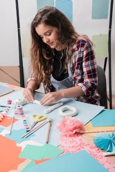 Primer plano de una mujer bonita haciendo manualidades utilizando arcilla blanca