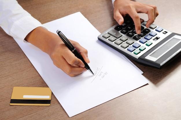 Primer plano de mujer calculando en calculadora y escritura
