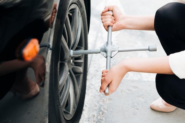 Primer plano de mujer cambiando neumáticos