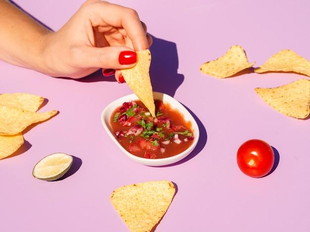 Primer plano mujer con chips de tortilla y salsa