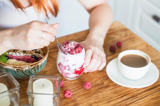 Primer plano de mujer comiendo yogurt con frambuesa en mesa de madera