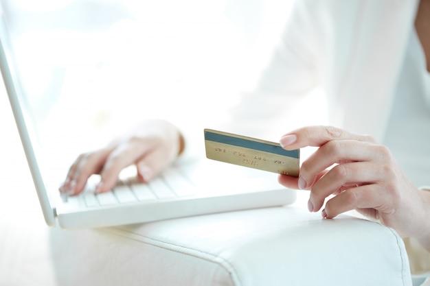 Primer plano de mujer comprando en línea con tarjeta y portátil