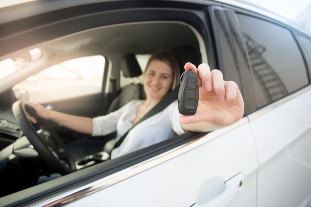 Primer plano de una mujer conductora mostrando las llaves del coche a través de la ventana abierta