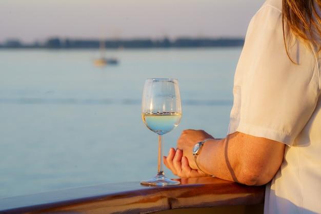 Primer plano de una mujer con una copa de vino en la cubierta de un barco