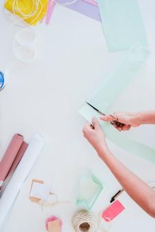 Primer plano de una mujer cortando el papel de la tarjeta con tijera