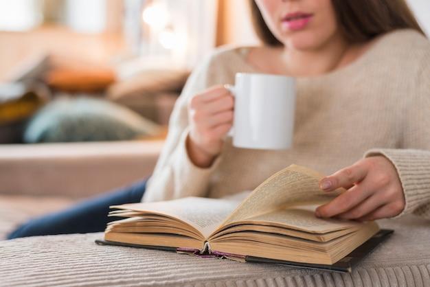 Primer plano de una mujer dando vuelta la página del libro que sostiene la taza de café en la mano