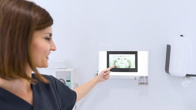 Primer plano de una mujer dentista apuntando a los dientes de rayos x en la clínica
