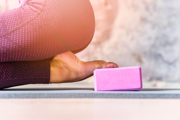 Primer plano de mujer deportiva practicando yoga usando bloque rosa