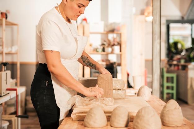 Primer plano de mujer desenvolviendo la arcilla en el taller.