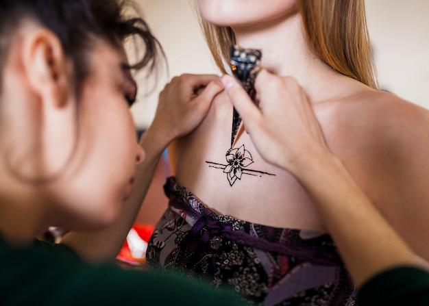 Primer plano de una mujer dibujando el tatuaje mehndi sobre el pecho femenino