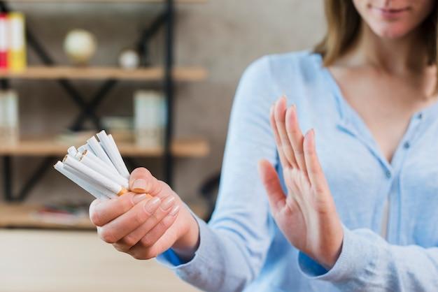 Primer plano de mujer diciendo que no sostiene manojo de cigarrillos en la mano