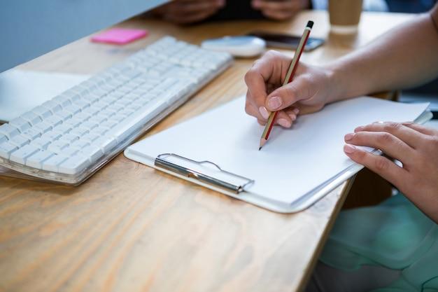Primer plano de mujer ejecutiva de negocios escribiendo en el portapapeles en el escritorio