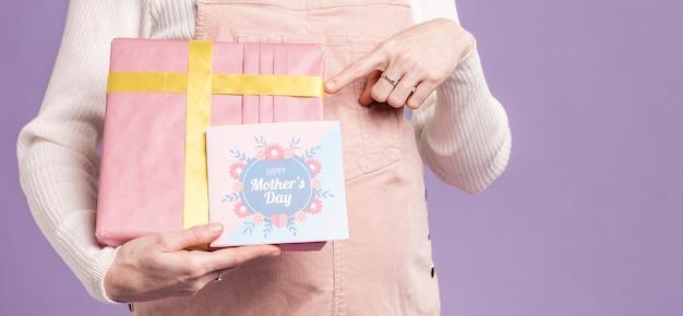 Primer plano mujer embarazada apuntando a regalo y tarjeta de felicitación