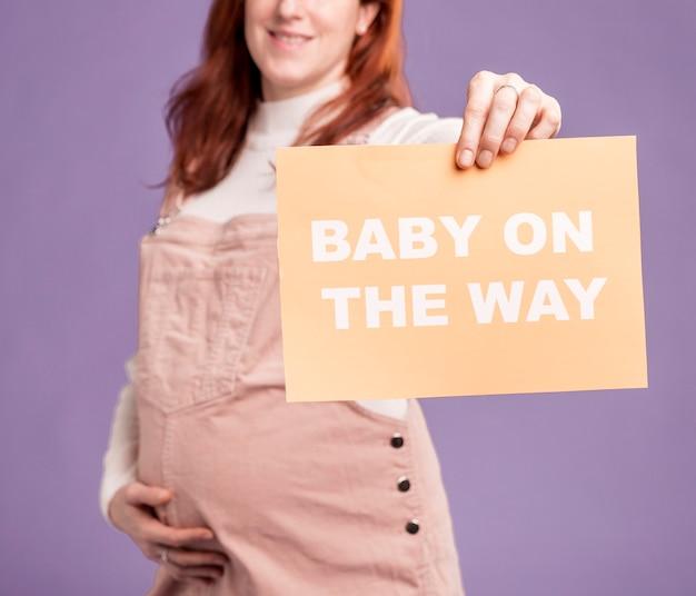 Primer plano mujer embarazada sosteniendo papel con bebé en el mensaje de camino