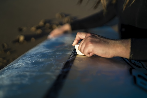 Primer plano de una mujer encerando su tabla de surf en la playa en españa