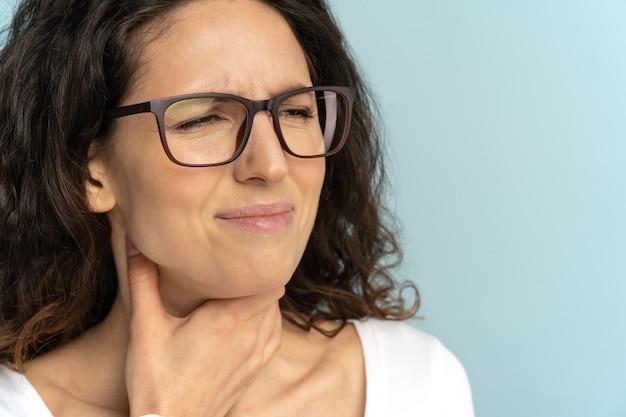 Primer plano de una mujer enferma con dolor de garganta amigdalitis, resfriado, sufriendo dolor al tragar