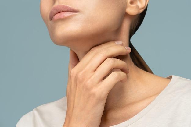 Primer plano de una mujer enferma con dolor de garganta, malestar, sosteniendo la mano sobre su cuello