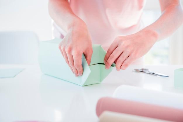 Primer plano de una mujer envolviendo la caja de regalo en mesa blanca