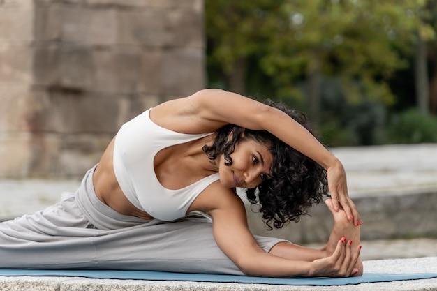 Primer plano de una mujer española practica yoga al aire libre