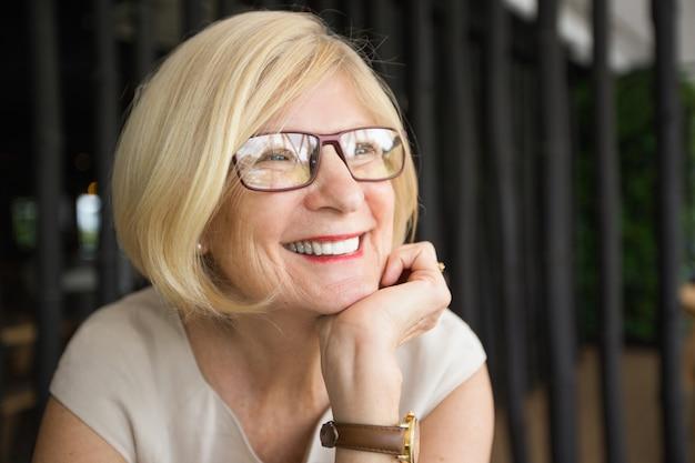 Primer plano de la mujer feliz atractiva senior en el café